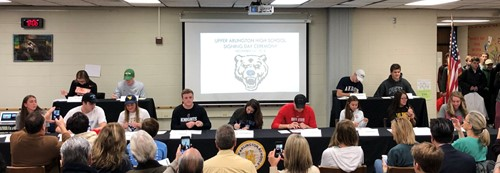 Student-athletes sitting at tables signing their commitment letters for National Signing Day