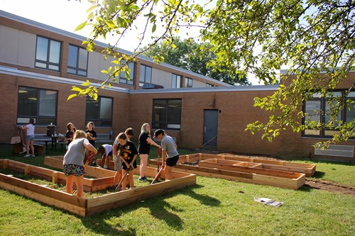 Students and staff working to dig a new community garden during HOP Day at Hastings Middle School