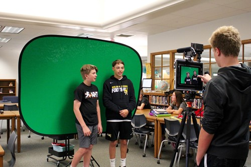 Two Jones Middle School students in front of a green screen while another student records on an iPad