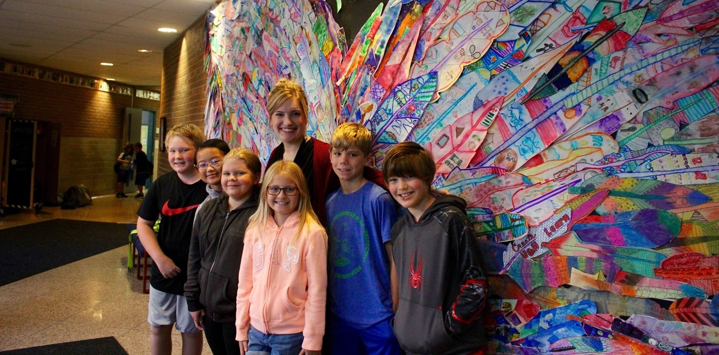 Art teacher Megan Taylor posing with students in front of the Windermere Wings