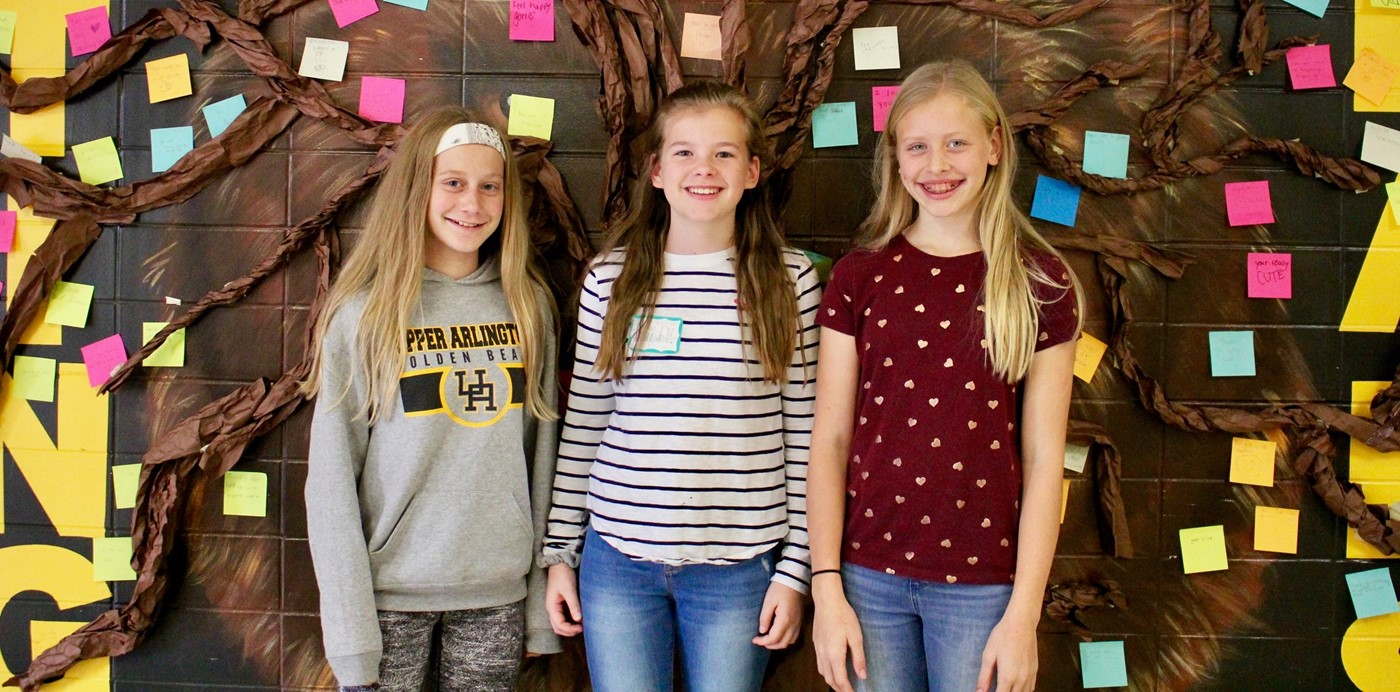 Three Hastings students posing in front of a Compliment Tree and the Hastings Bear