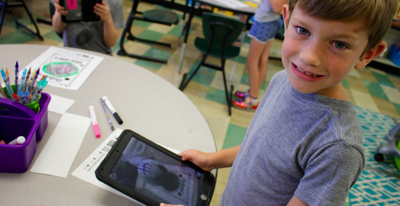 A boy making a three-dimensional dot using an app on his iPad for Dot Day
