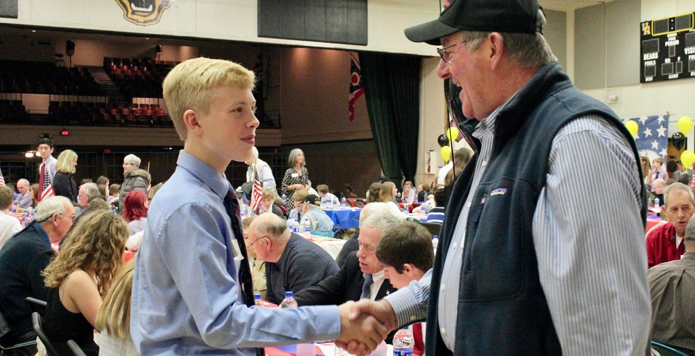Student shaking a veteran's hand at the 8th grade Veterans Day luncheon