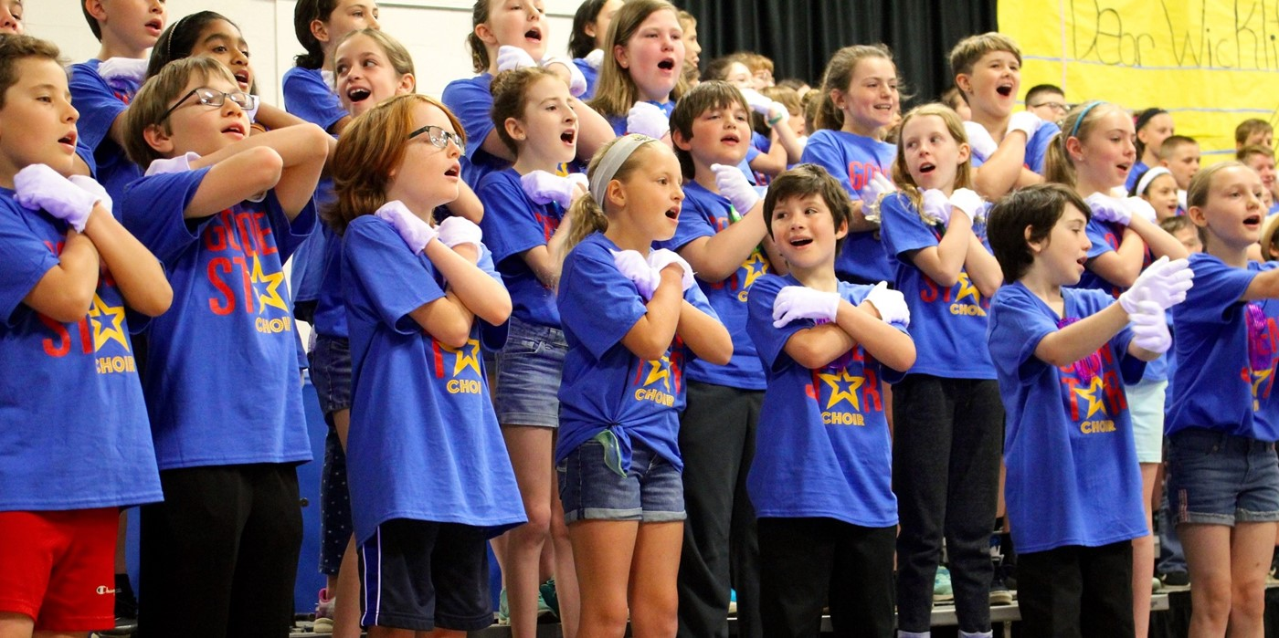 Children smiling during a choir performance