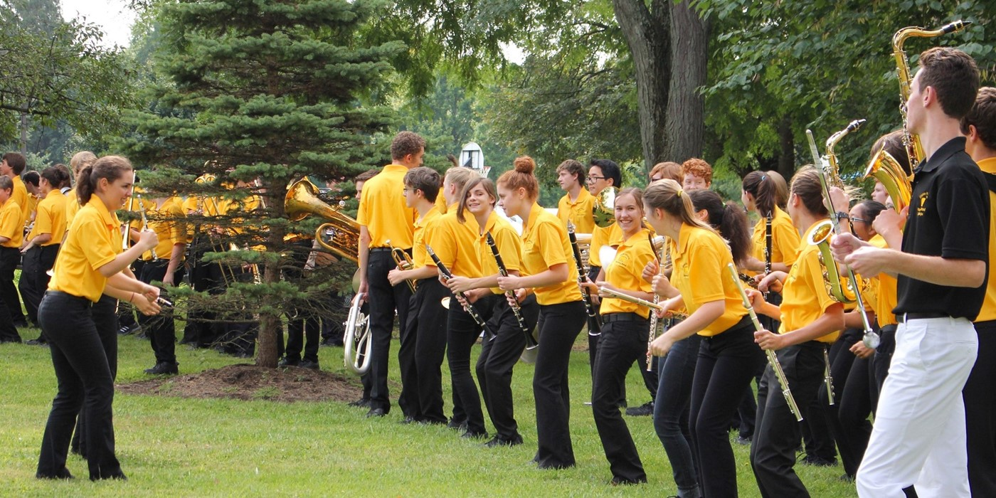 The UAHS Marching Band performing outdoors for elementary students