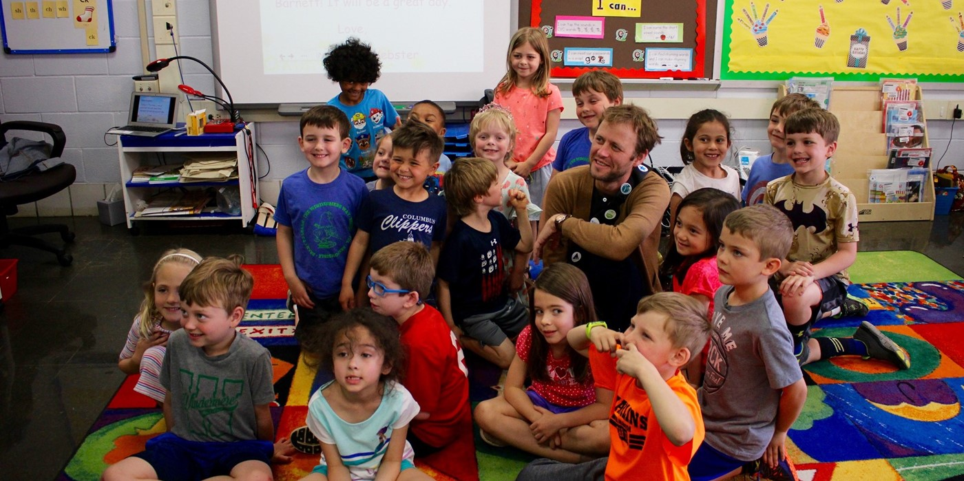 Author Mac Barnett posing with a kindergarten class