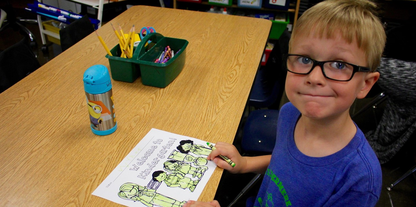 A boy working on a kindergarten worksheet