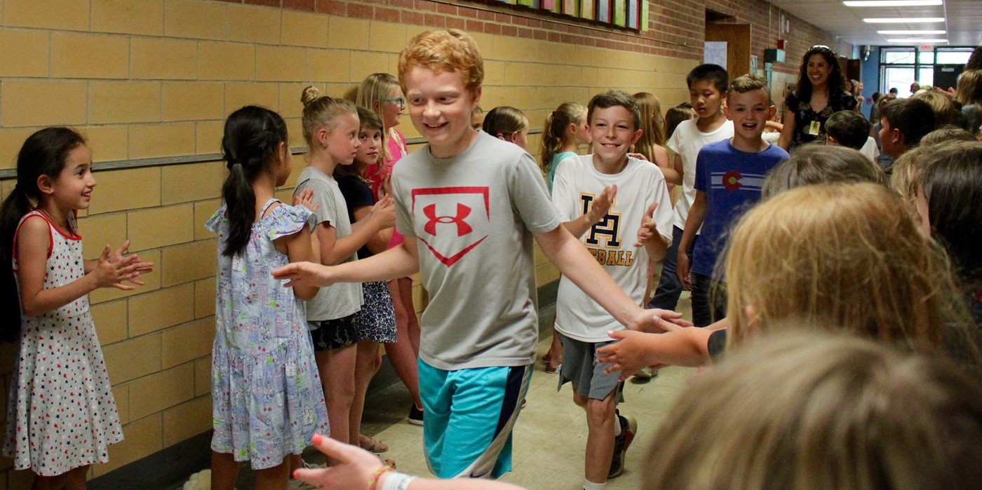 Fifth-graders getting high-fives from other students on the last day of school
