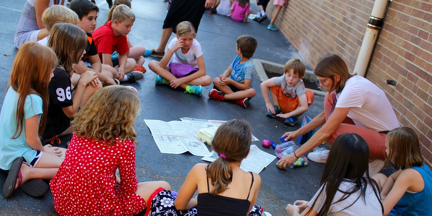 A circle of students learning outdoors