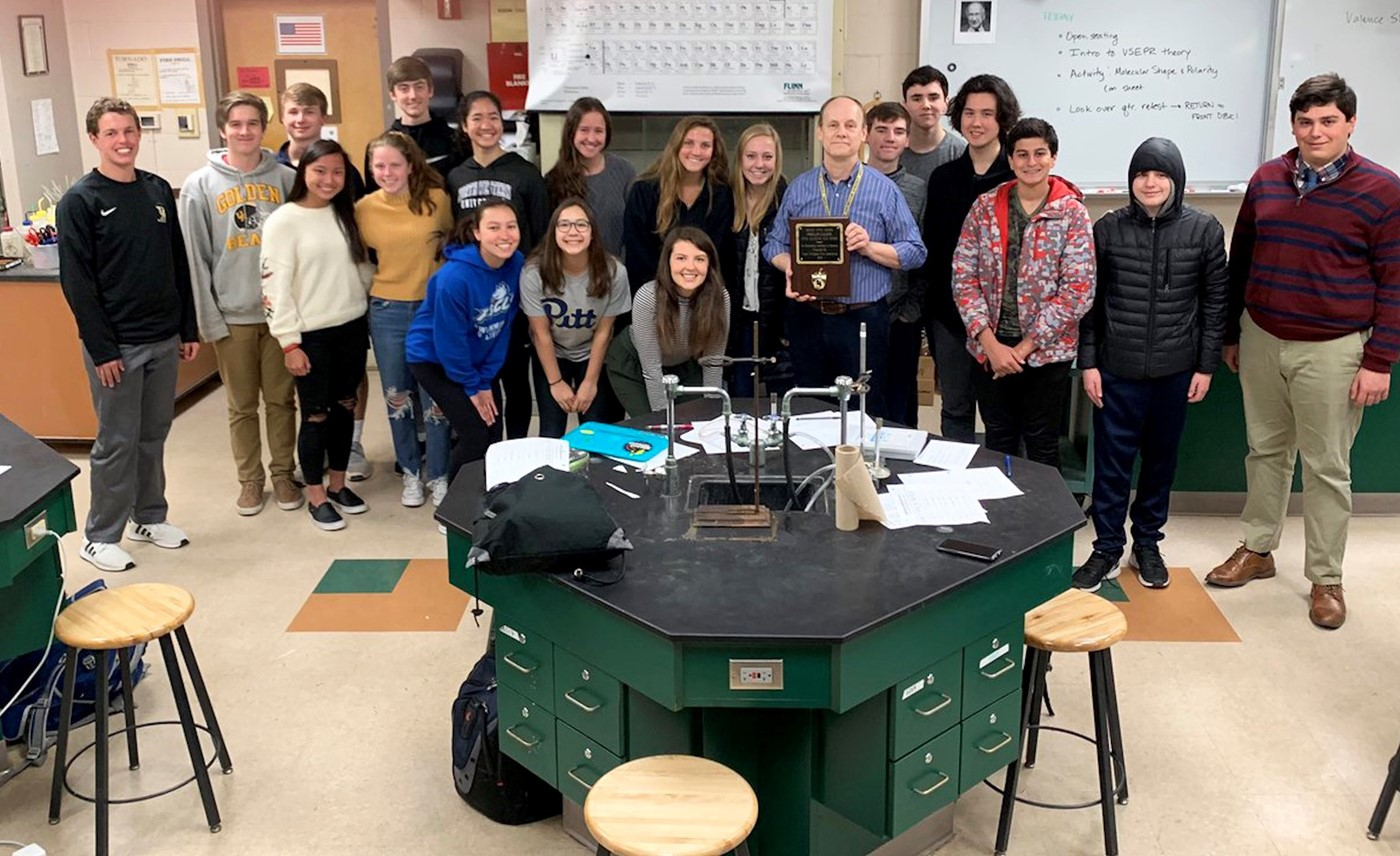 a photo of Mr. Lampe and students, golden apple award