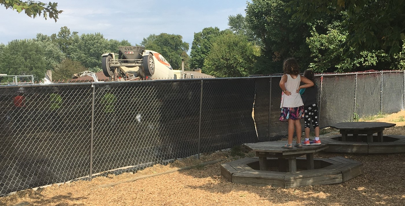 Two girls watching cement truck from playground during Wickliffe SACC