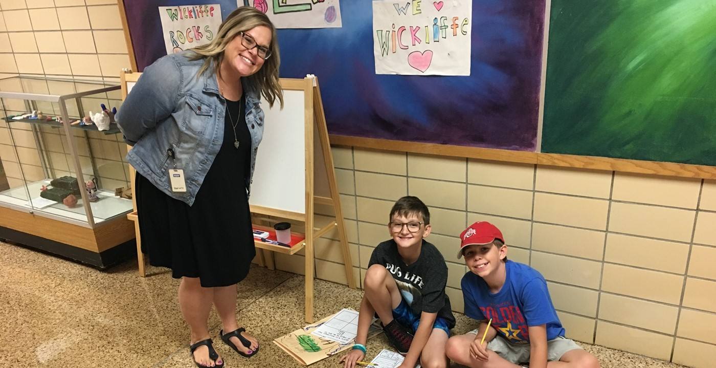 Teacher with two students doing art in hallway