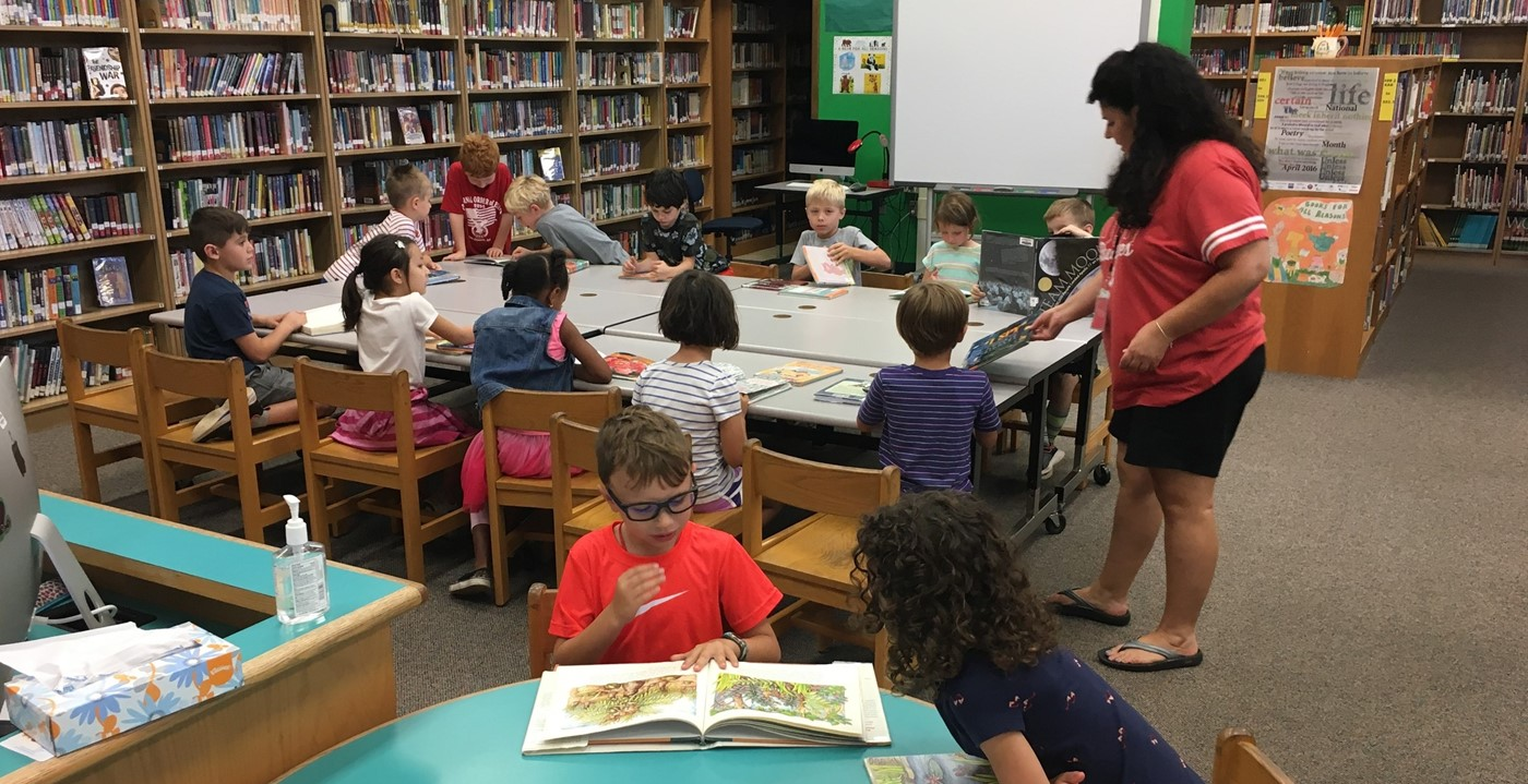 Teacher with class reading books in library