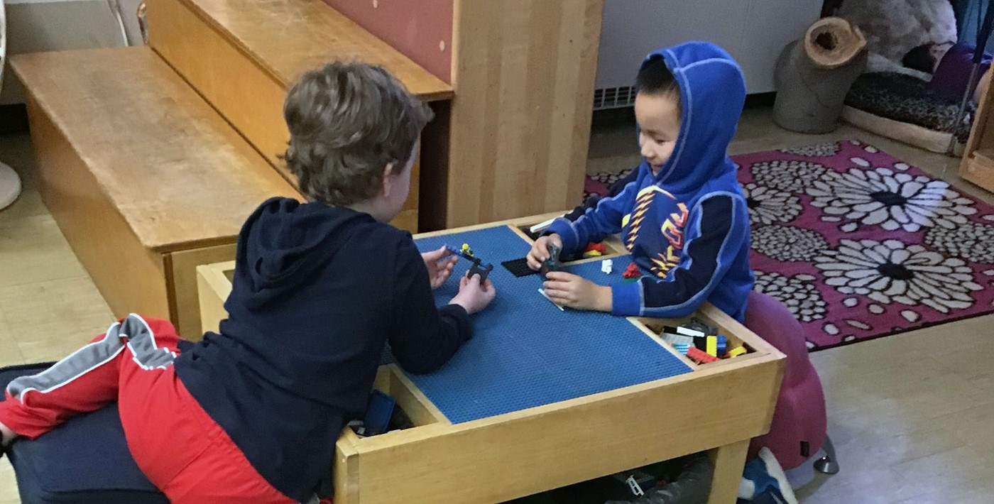 Two children playing at a block table