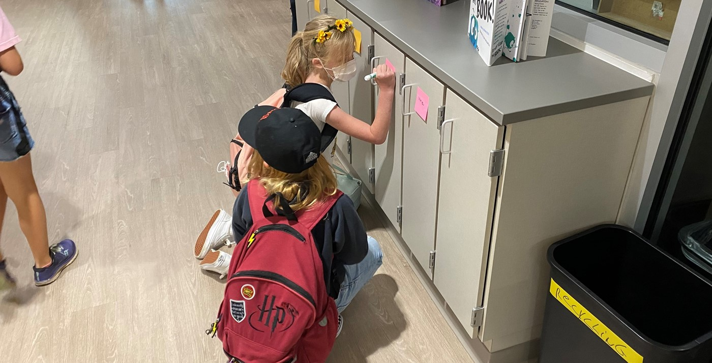 Students writing names on lockers